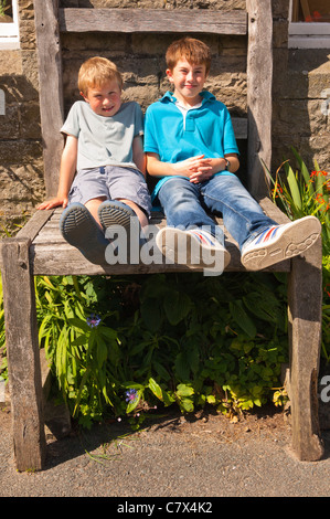 Two boys sit on the giant chair outside the Old School Crafts Shop at Muker in Swaledale in North Yorkshire , England - Stock Photo