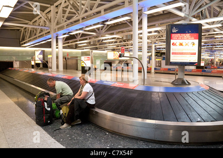 2 passengers sitting on the baggage carousel in the collection area having probably lost their luggage, Heathrow - Stock Photo