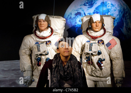 Tourist posing with waxworks of Neil Armstrong and Buzz Aldrin  at Madame Tussauds waxworks, Washington DC USA - Stock Photo
