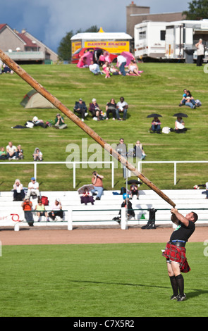 Gregor Edmunds, heavyweight athlete, tossing the caber at Cowal Highland Gathering, 2011 - Stock Photo
