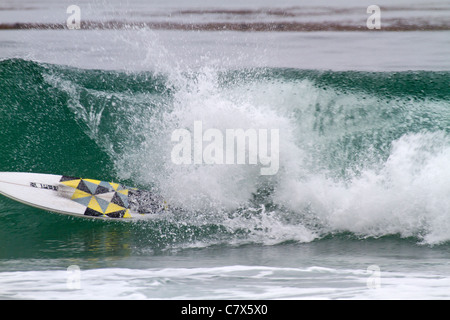 Surfer underwater with just surf board showing after riding a wave near Carmel Beach, California - Stock Photo
