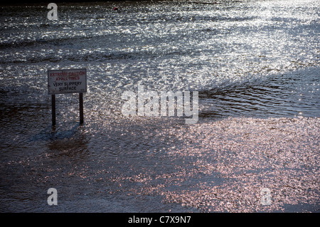 slippery surface sign in water - Stock Photo