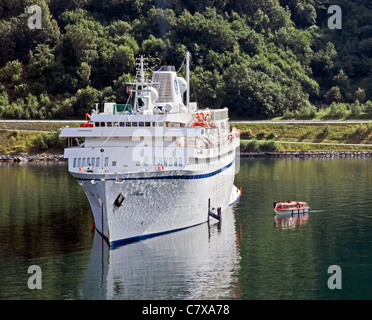 Cruise ship Athena is moored on the Aurlandsfjorden at Flaam in Western Norway with a tender arriving with passengers - Stock Photo