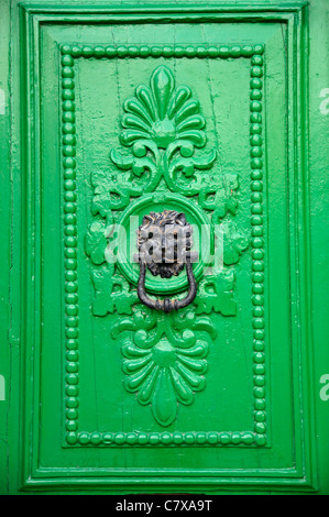 Black lion head door knocker on green door in Valletta, Malta.
