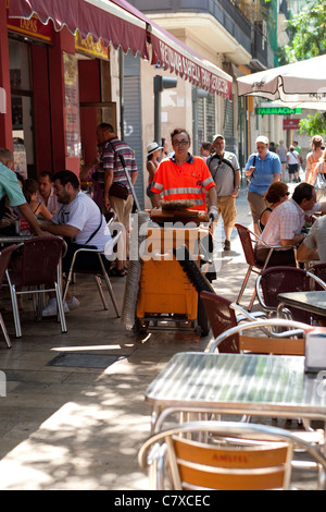 Woman Pavement sweeper passing sidewalk cafe Valencia Spain - Stock Photo