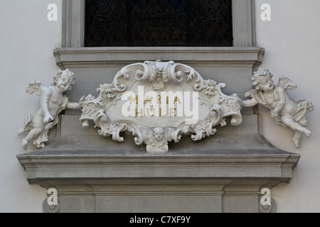 A baroque shield held by angels on a church in the city of Vienna indicating the name of the district 'mary help' - Stock Photo