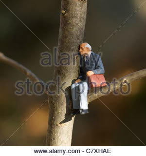 Solitary elderly male figure alone sitting in tree with briefcase - Stock Photo