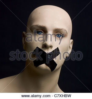 A male dummy with sticking plaster over mouth - Stock Photo