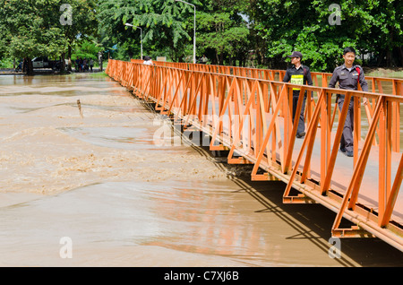 Two Thai policeman walking on bright orange metal footbridge at flooded Ping River dam south of Chiang Mai in northern - Stock Photo