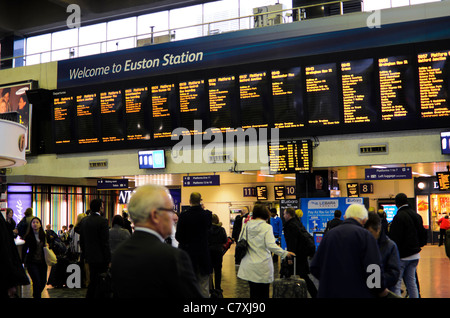 Passengers check departure times in the concourse of Euston Station, London, England. - Stock Photo
