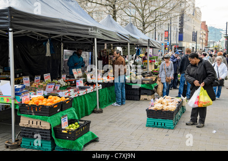 Outdoor market stalls in Piccadilly Gardens, Manchester, England. Customers represent the wide ethnic diversity - Stock Photo