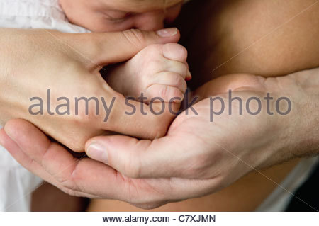 close-up of a mother and father's hands holding a baby's hand with the baby's face in the background - Stock Photo