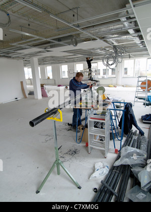 Two men installing cables and tubes in the ceiling of a brand new office building - Stock Photo