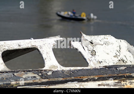 Speed boat launch with old wreck in foreground - Stock Photo