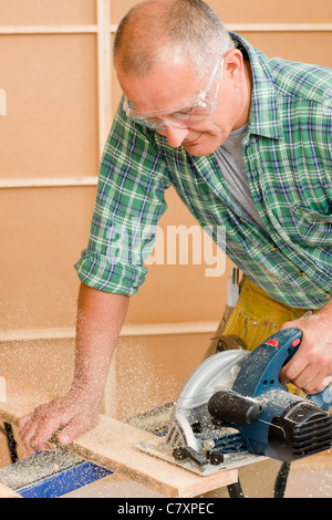 Handyman mature home improvement cut wood with jigsaw - Stock Photo