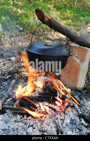 camp fire and cooking in a pot - Stock Photo