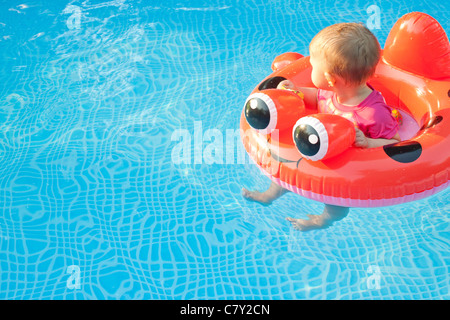 Small child in floatation device looking away while floating in a pool alone - Stock Photo