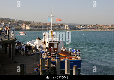 Passengers boarding a day trip boat the Dorset Belle on Swanage Bay on the Dorset coast southern England UK - Stock Photo