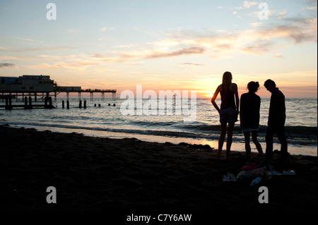 Silhouettes of three young people watching the sunset over Cardigan Bay, Aberystwyth Wales UK. - Stock Photo