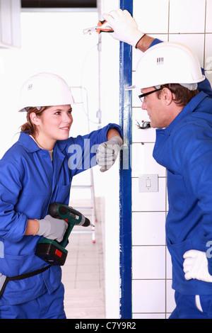 Supervisor training worker apprentice on solar panel ...