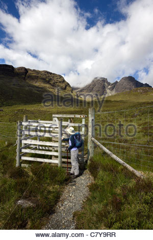 Hillwalker by kissing gate in deer fence on the path to Blaven in the Black Cuillin mountains on the Isle of Skye, - Stock Photo