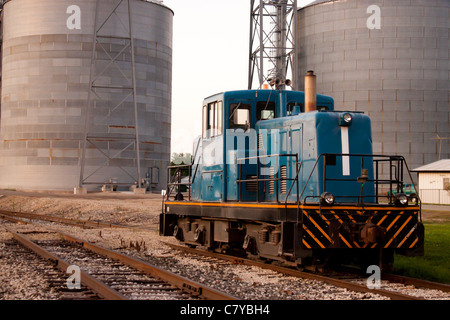 Train head car stopped on tracks in front of grain mill - Stock Photo