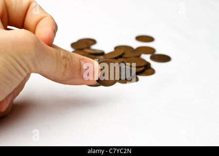 Person pinching a wheat penny in front of a small pile of wheat pennies on a white background - Stock Photo