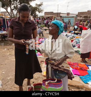 Two African women complete a market transaction using M-Pesa, a mobile-phone based money transfer service - Stock Photo