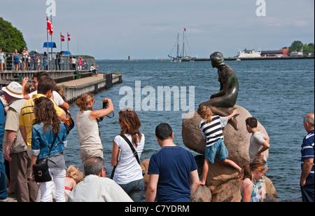 Tourists surround the Little Mermaid statue in Copenhagen Harbor - Stock Photo
