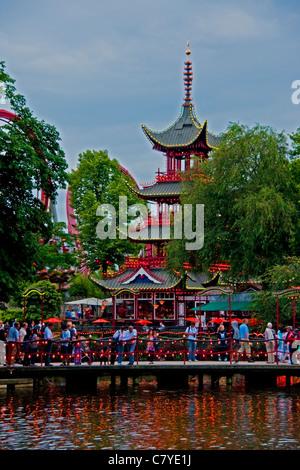 Bridge on Dragon Boat Lake in Tivoli Gardens amusement park with pagoda and roller coaster - Stock Photo