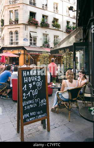 People enjoying a drink at a cafe terrace in Paris, France - Stock Photo