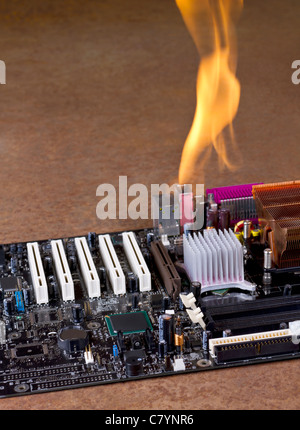burning computer mainboard in rusty background - Stock Photo