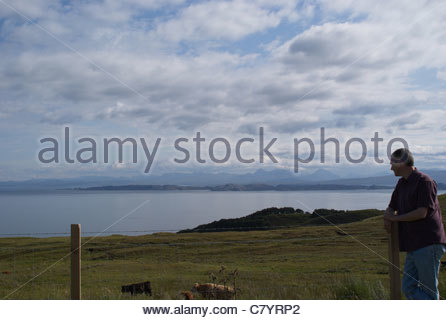 Man in 30's standing, looking out to sea, North of Portree, North west coast of The Isle of Skye, Inner hebrides, - Stock Photo