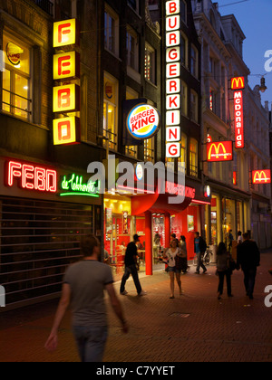 Fast food signs at night on the Nieuwendijk in the city centre of Amsterdam, the Netherlands. - Stock Photo