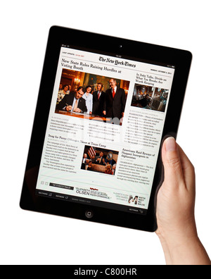 Hand holding iPad showing the New York Times newspaper app - Stock Photo