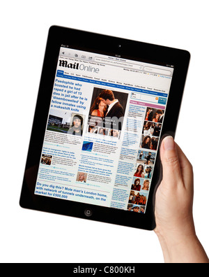 Hand holding iPad showing the Daily Mail newspaper online website - Stock Photo