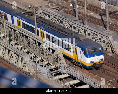Dutch NS 'sprinter' commuter train crossing a bridge in Amsterdam, the Netherlands - Stock Photo