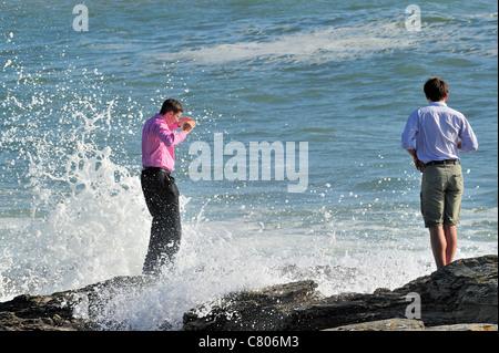 Tourist getting soaking wet from wave crashing on rocks, Pointe Saint-Gildas / Saint Gildas Point, Loire-Atlantique, - Stock Photo