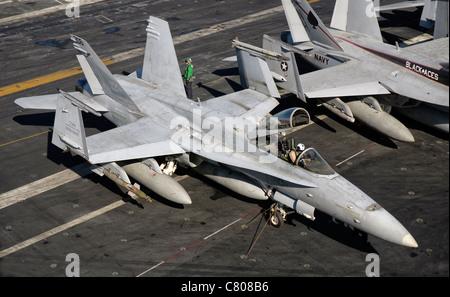 A US Navy F/A-18C Hornet parked on the flight deck of aircraft carrier USS Nimitz. - Stock Photo