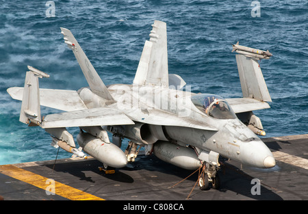 A US Navy F/A-18C Hornet tied down on the flight deck of aircraft carrier USS Nimitz. - Stock Photo