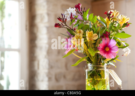Colour photo of a fresh bouquet of flowers set inside on the kitchen table on a spring morning in France. - Stock Photo