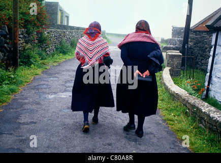 Two women wearing traditional dress walk home from daily Mass on one of the Aran Islands in Co Galway Ireland - Stock Photo