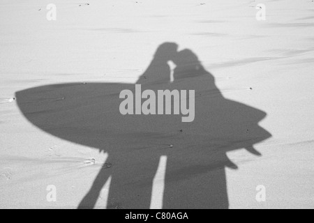 Black and white photo of a shadow on the sand of a couple kissing and carrying a surfboard. - Stock Photo