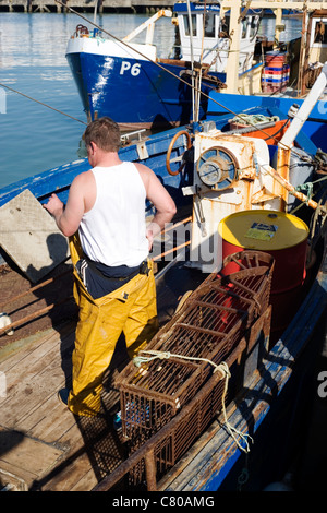 deep sea fisherman working on his boat in harbour - Stock Photo