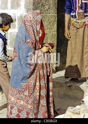 Veiled woman wearing an abaya in the Old City of Sana'a, Yemen - Stock Photo