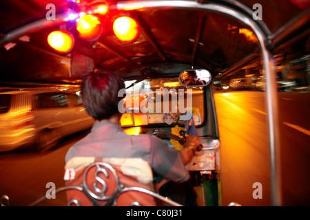 Thailand, Bangkok, Tuk Tuk Taxi Driver at night - Stock Photo
