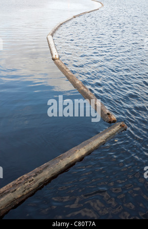log boom barrier floating on water - Stock Photo