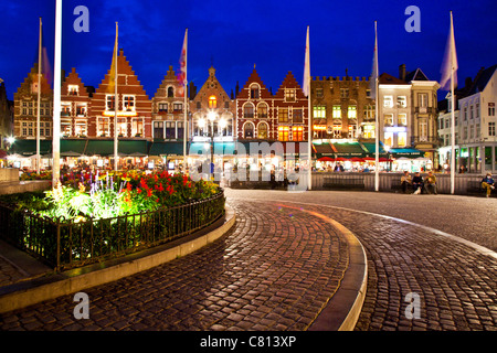 Bars, cafes, restaurants, and tourists in the Grote Markt or Market Square in Bruges, (Brugge), Belgium at twilight. - Stock Photo