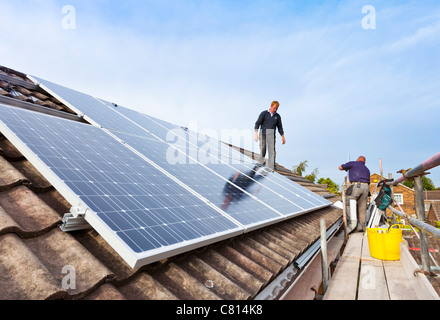 fitting solar panels on detached house roof england uk gb eu europe - Stock Photo