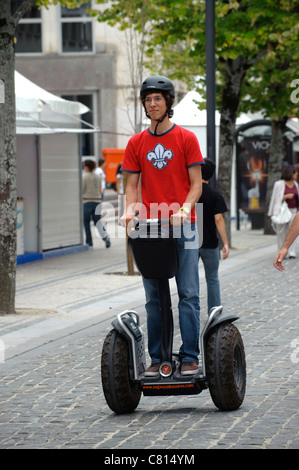Man riding Segway in busy street - Stock Photo